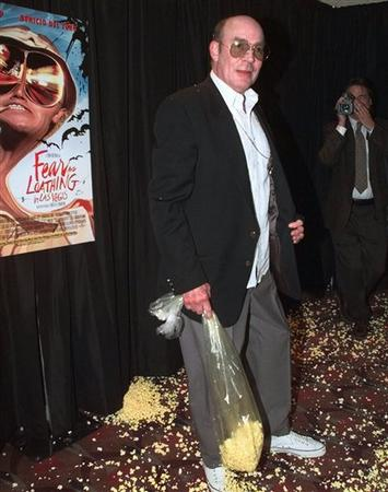 "Author Hunter S. Thompson stands in a pile of popcorn after hurling a bag of it at Johnny Depp and Benicio del Toro, co-stars of the movie based on his book, ""Fear and Loathing in Las Vegas,"" at the movie's premier Tuesday, May 19, 1998 in New York."